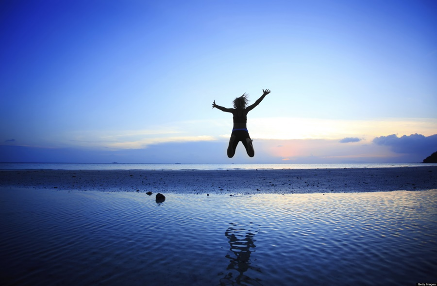 Silhouette of woman jumping high in the air at beach.