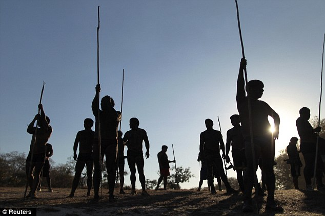 Prepared: Yawalapiti men stand with their spears on the bank of the Tuatuari river