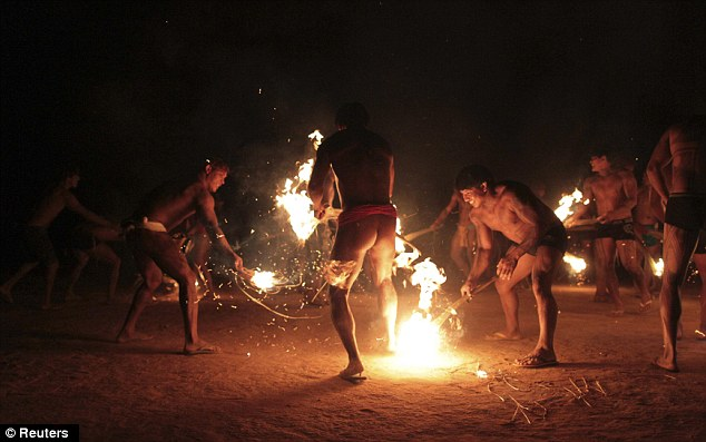 Playing with fire: Yawalapiti men perform a ceremony between cousins during the celebration of this year's quarup