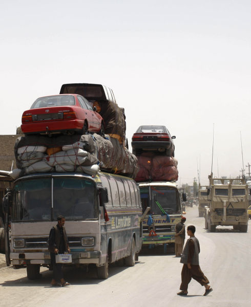 Passenger buses are loaded with cars for transport in Kandahar, May 26, 2009. REUTERS/Jorge Silva (AFGHANISTAN SOCIETY TRANSPORT IMAGES OF THE DAY) - RTXO3NF