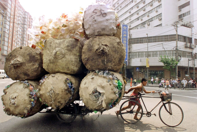 An enterprising Chinese man pulls a bicycle cart packed high with bags of recyclable plastic containers in Shanghai July 25, 2002. The man sells each kilogram (2.2 pounds) of plastic for 0.08 yuan ($.01) to a nearby depot. REUTERS/Claro Cortes IV CC/JD - RTR846W