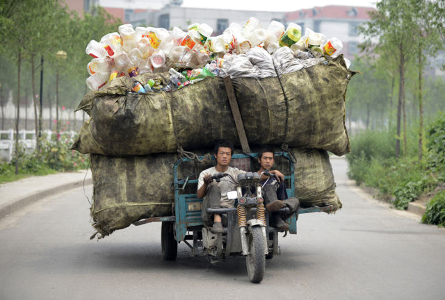 A motor tricycle loaded with recyclable plastic bottles drives along a street in Taiyuan, Shanxi province, July 18, 2012. REUTERS/Stringer (CHINA - Tags: ENVIRONMENT SOCIETY TPX IMAGES OF THE DAY) CHINA OUT. NO COMMERCIAL OR EDITORIAL SALES IN CHINA - RTR3517N