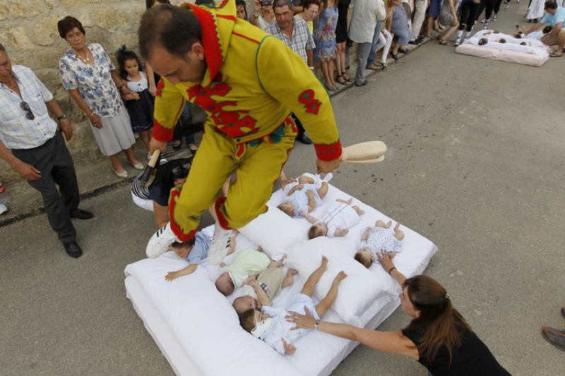 A man dressed up as the devil jumps over babies lying on a mattress in the street during 'El Colacho', the 'baby jumping festival' on June 26, 2011 in the village of Castrillo de Murcia, near Burgos. Baby jumping (El Colacho) is a traditional Spanish practice dating back to 1620 that takes place annually to celebrate the Catholic feast of Corpus Christi. During the act - known as El Salto del Colacho (the devil's jump) or simply El Colacho – men dressed as the Devil (known as the Colacho) jump over babies born the last twelve months of the year who lie on mattresses in the street. AFP PHOTO / CESAR MANSO